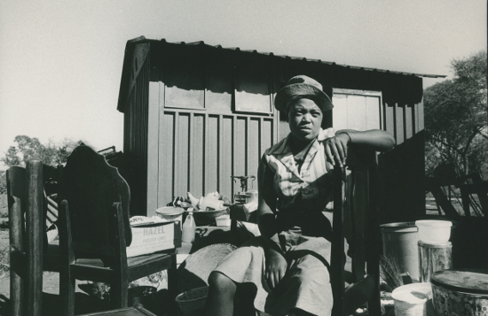 Women sits amongst her possessions after removal to Pachsdraai. 1984. Photographer: Paul Weinberg. AL2547_20.1.9