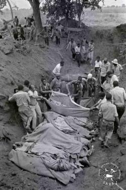 Bodies of bombing victims being moved into a mass grave after the Freedom Camp massacre