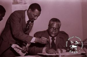 Joshua Nkomo and Amos Ngwenya signing the oath agreement in Lusaka, Zambia