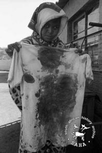 Mrs Mazibuko holds the bloody t-shirt of her son who was shot and killed by police, June 1985. Archived as SAHA collection AL3274_C26.2