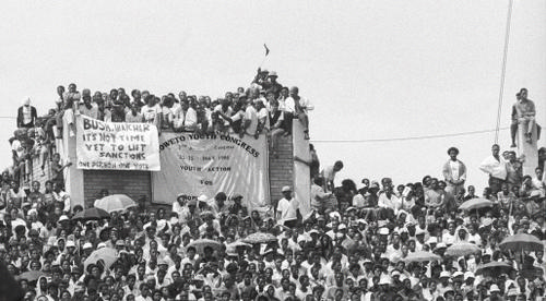 Youth sitting on top of a high wall during a welcome home Rally for Mr Nelson Rolihlahla Mandela in Soccer City, 1990-02-13 AL2878_H01.31