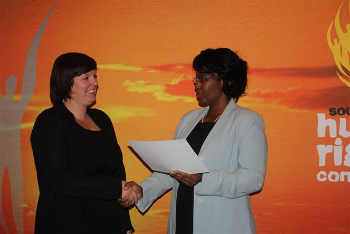 Former AVI volunteer, Tammy O'Connor accepting an award on behalf of SAHA from the South African Human Rights Commission's representative.