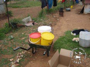 Three buckets carrying water loaded in a wheelburrow